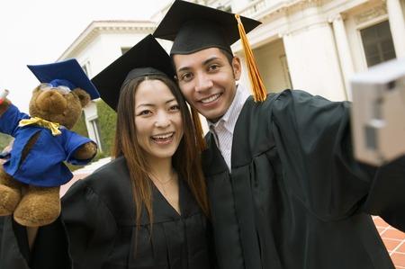 alumnae: Friends Taking Picture Together at Graduation LANG_EVOIMAGES