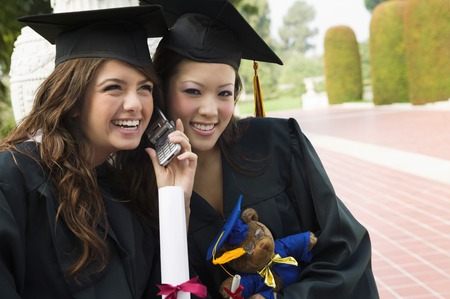 aspirational: Graduates Listening to Cell Phone LANG_EVOIMAGES