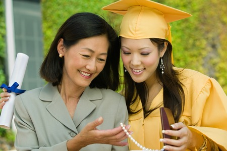 alumnae: Mother and Daughter Admiring Gift at Graduation LANG_EVOIMAGES
