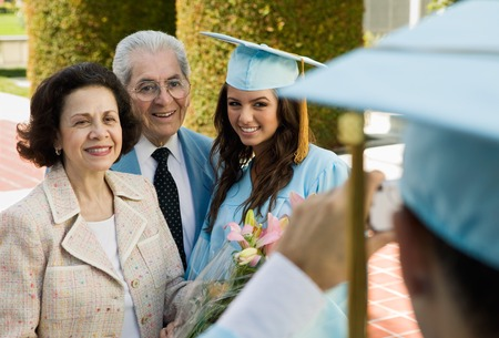 succeeding: Graduate Posing for Picture with Parents