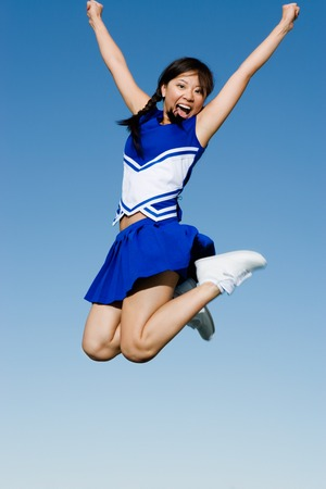 lifted hands: Cheerleader Performing Cheer in Mid-Air