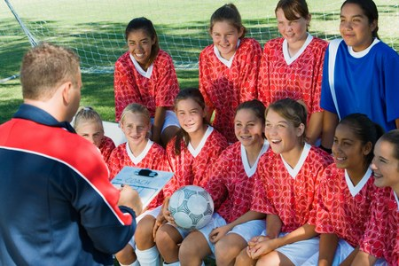 Coach Giving Pep Talk to Smiling Soccer Team Stock Photo - 5435735
