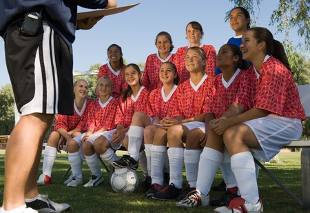 or instruction: Girls Soccer Team Listening to Coach