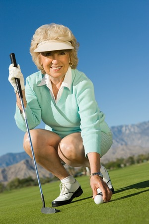 athletic gear: Woman Picking up Golf Ball