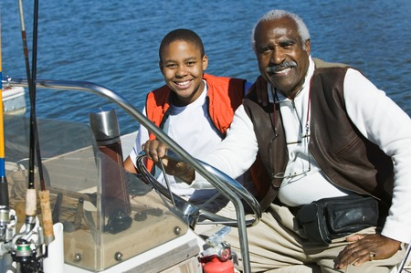 early 60s: Grandfather Taking Grandson Fishing in Boat