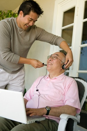 Son Adjusting Headphones on Father Stock Photo - 5435827