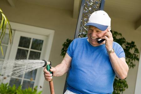 Senior Man Watering Yard and Using Cell Phone Stock Photo - 5435829