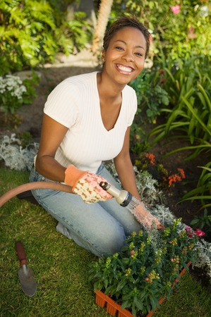 garden hose: Woman Watering New Plants LANG_EVOIMAGES
