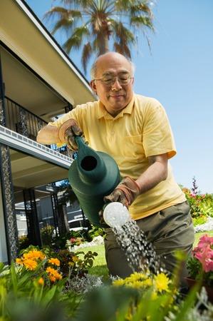 asian gardening: Man Watering Garden LANG_EVOIMAGES
