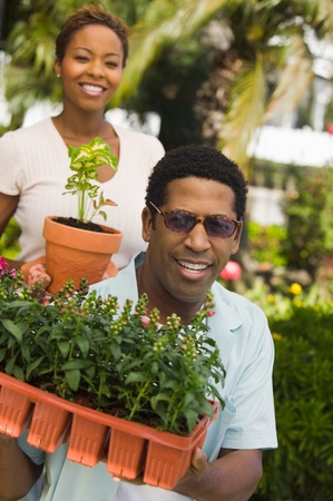 early 30s: Couple Holding New Plants