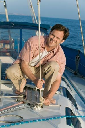Man on Sailboat Tying Rope Stock Photo - 5435899
