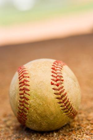 athletic gear: Baseball Sitting on Dirt LANG_EVOIMAGES