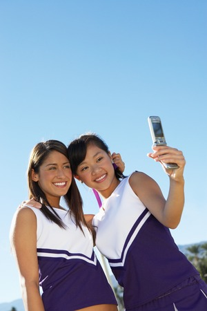 fervour: Two Cheerleaders Taking Photo of Themselves with Camera Phone LANG_EVOIMAGES