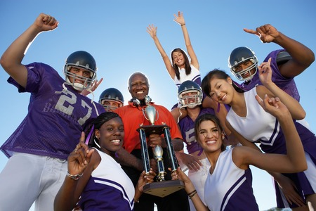 Cheerleaders and Football Players Celebrating with Coach