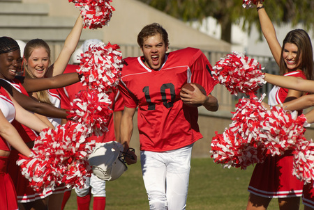 pompom: Football Player Running Through Cheerleaders LANG_EVOIMAGES