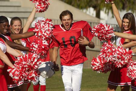 fervour: Football Player Running Through Cheerleaders LANG_EVOIMAGES