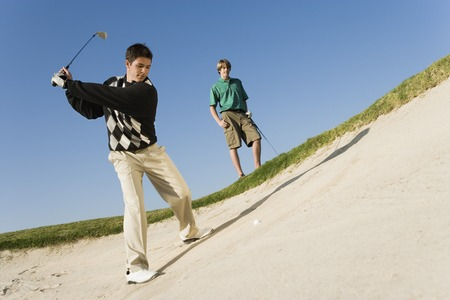 twentysomething: Young Man Hitting Ball in Sand Trap