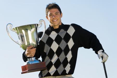 accomplishing: Golf Tournament Champion Holding Trophy LANG_EVOIMAGES