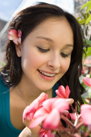 Beautiful Young Woman Smelling Flowers