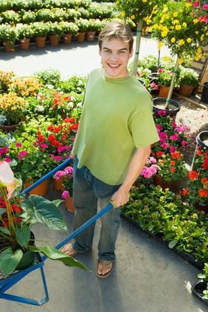 nurseries: Young Man Pushing Wheelbarrow at Nursery