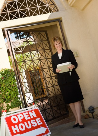 late thirties: Real Estate Agent at Open House LANG_EVOIMAGES