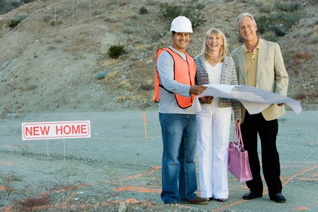 Builder and Couple at New Home Construction Site Stock Photo - 5436127