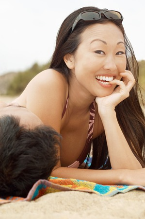 Smiling Woman Lying Next to Man on Beach Stock Photo - 5436138