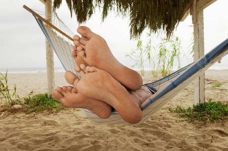 barefoot: Par de pies en borde de la hamaca en la playa