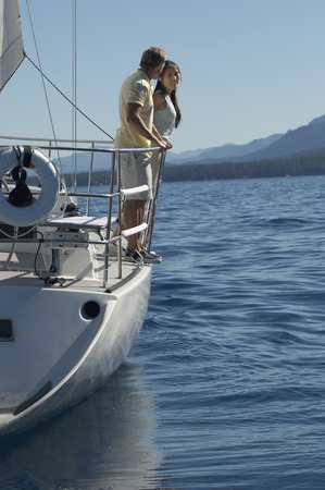 Couple Standing on Side of Sailboat Stock Photo - 5436156