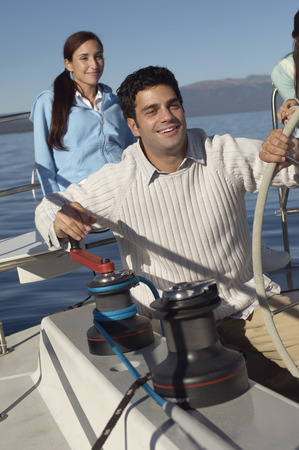 Man Turning Winch on Sailboat Stock Photo - 5436160