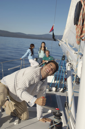 Man Raising Sail on Mountain Lake Stock Photo - 5436161