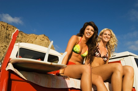 Two Young Women Sitting in Back of Truck Stock Photo - 5436192