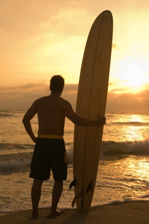 surfers: Longboard Surfer Enjoying Sunset on Beach LANG_EVOIMAGES