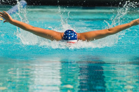 exerting: Woman Swimming Butterfly Stroke