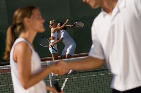 two people with others: Tennis Players Shaking Hands at Net LANG_EVOIMAGES
