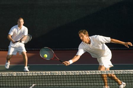 exerting: Tennis Player Swinging at Ball