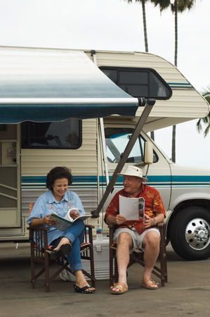 early 60s: Couple Relaxing Outside Their RV