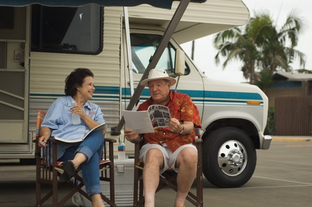late sixties: Couple Relaxing Outside Their RV