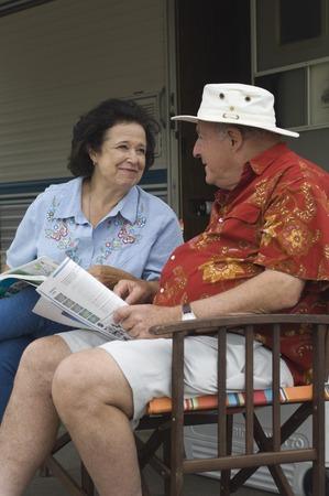 the ageing process: Senior couple sitting beside caravan LANG_EVOIMAGES