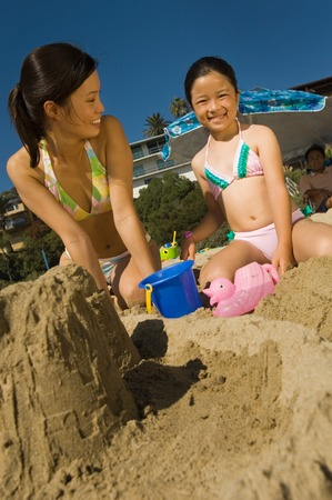 Woman Building Sandcastle With Daughter Stock Photo - 5436302