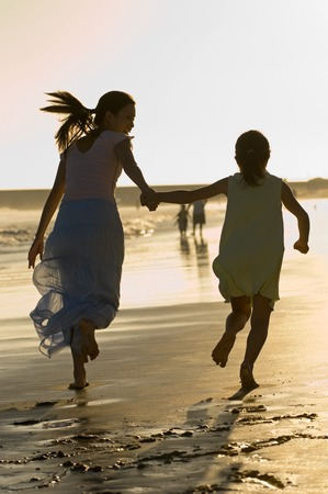 fond of children: Woman Running on Beach With Daughter LANG_EVOIMAGES