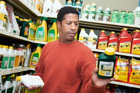 pesticides: Man Choosing Plant Care Products LANG_EVOIMAGES