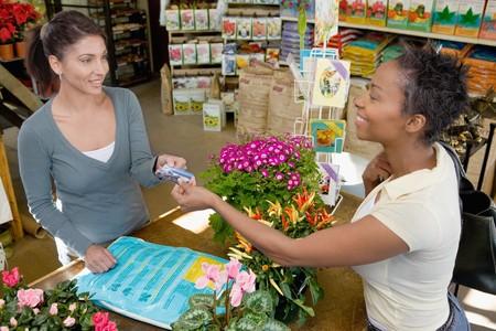 transaction: Woman doen van een aankoop bij Plant Nursery