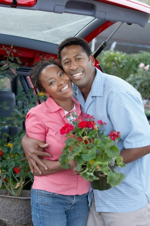 late forties: Couple Loading Potted Plants into Trunk of Car