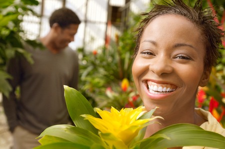 smiling woman in a greenhouse: Smiling Woman in a Greenhouse LANG_EVOIMAGES