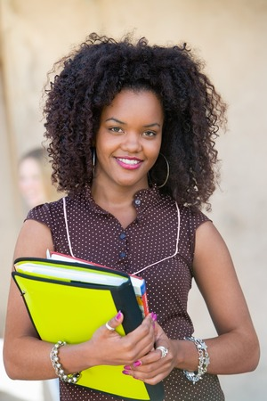 Student Holding Notebook and Textbooks Stock Photo - 5438123