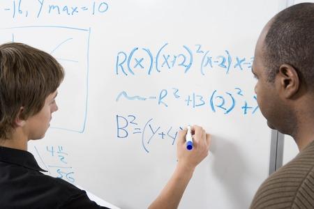 ホワイト ボード上の家庭教師と数学の方程式を書く学生