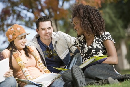 Young students sitting on grass Stock Photo - 5438208