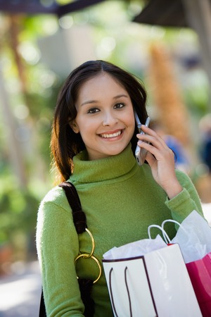 Woman with Shopping Bags Using Cell Phone Stock Photo - 5438227