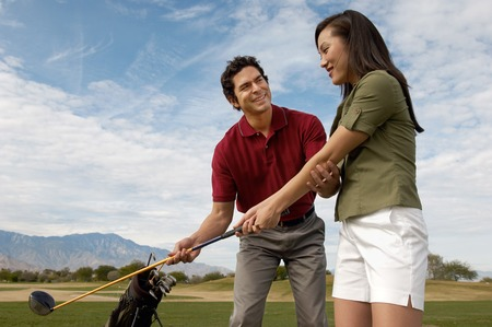 golf equipment: Woman Getting a Golf Lesson LANG_EVOIMAGES
